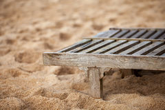 Empty wooden deck chair on the beach. With sand Royalty Free Stock Photography