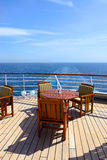 Empty wooden deck chairs and table on ship Stock Photos