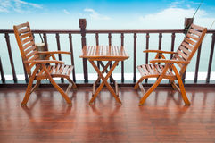 Empty wooden deck chairs and table on ship. Royalty Free Stock Image