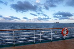 Empty wooden deck and railing with a life ring hanging on the ra. Il on a passenger boat or cruise ship, with  ocean in a travel concept Stock Photography
