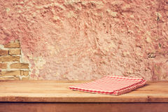 Empty wooden deck table with checked napkin over vintage wall Stock Photos