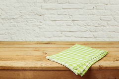Empty wooden deck table with checked tablecloth over brick wall background Royalty Free Stock Photography