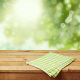 Empty wooden deck table with checked tablecloth over green nature bokeh background Stock Photography