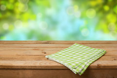Empty wooden deck table with checked tablecloth over green nature bokeh background for product montage Royalty Free Stock Images