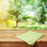 Empty wooden deck table with checked tablecloth over green park bokeh background for product montage royalty free stock photos
