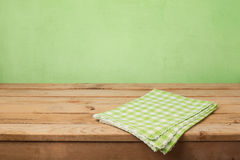 Empty wooden deck table with checked tablecloth over green wall background. For product montage display stock photos