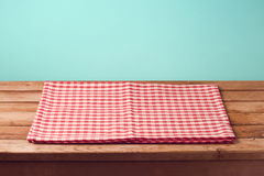 Empty wooden deck table with checked tablecloth over mint background for product montage Royalty Free Stock Photo
