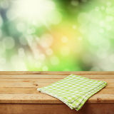 Empty wooden deck table with checked tablecloth over nature bokeh background for product montage Royalty Free Stock Photography