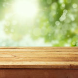 Empty wooden deck table with foliage bokeh
