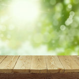 Empty wooden deck table with foliage bokeh background for product display montage. Spring or summer. Concept stock images