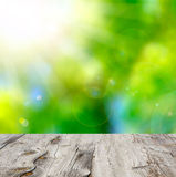Empty wooden deck table with foliage bokeh background. Stock Photos
