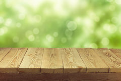 Empty wooden deck table with foliage bokeh background. Ready for product display montage. stock photo