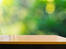 Empty wooden deck table with foliage bokeh background. Ready for product display present Stock Photography