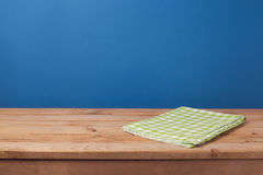 Empty wooden deck table with green checked tablecloth over blue wall background Royalty Free Stock Photo