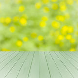 Empty wooden deck table with green and yellow soft focus background. Ready for product display montage. Stock Images
