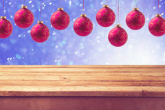 Empty wooden deck table with hanging ball decorations. Ready for product display montage. Christmas background. Empty wooden deck table with hanging ball Royalty Free Stock Images