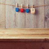 Empty wooden deck table with Hanukkah dreidel spinning top hanging on string Stock Photos