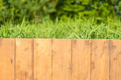 Empty wooden deck table. Wooden deck table over beautiful green background Royalty Free Stock Photos