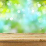 Empty wooden deck table over blurred bokeh nature background. For product montage display stock photos