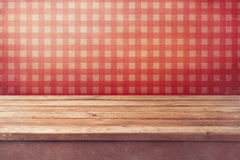 Empty wooden deck table over checked red wallpaper. Vintage kitchen interior.