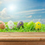 Empty wooden deck table over Easter eggs on grass. Egg hunt concept background Stock Photos