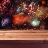 Empty wooden deck table over fireworks background. New Year eve celebration Stock Photos