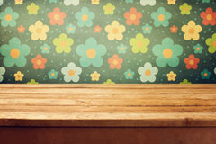 Empty wooden deck table. Over floral print wallpaper stock image