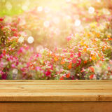 Empty wooden deck table over flowers bokeh background for product montage display. Spring or summer season. Concept stock photos