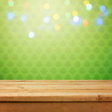 Empty wooden deck table over green shamrock wallpaper background with bokeh lights overlay. St. Patricks day concept. For product monatge display stock photography