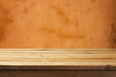 Empty wooden deck table over old yellow orange wall Royalty Free Stock Photography
