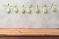 Empty wooden deck table over rustic wall background with eggs decoration garland. Easter holiday Stock Photos