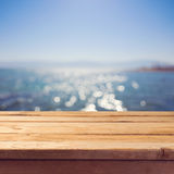 Empty wooden deck table over sea bokeh background. Summer holiday vacation. Background Stock Image