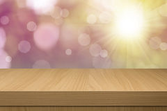 Empty wooden deck table over sunset bokeh background Stock Image