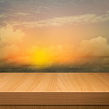 Empty wooden deck table over sunset cloudy sky background Stock Images