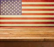 Empty wooden deck table over USA flag background. Independence day, 4th of July background. stock photos