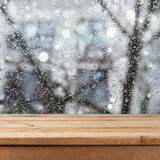 Empty wooden deck table over wet glass window. Rainy weather concept. Stock Image