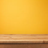 Empty wooden deck table over yellow wallpaper Stock Photos