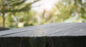 Empty wooden deck table with park bokeh Stock Images