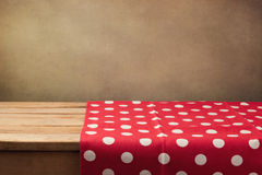 Empty wooden deck table with polka dots tablecloth over grunge background stock photography