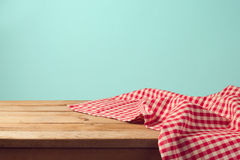 Empty wooden deck table and red checked tablecloth. Over mint wallpaper background Royalty Free Stock Image
