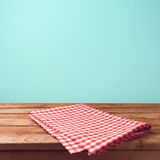 Empty wooden deck table and red checked tablecloth. Over mint wallpaper background royalty free stock images