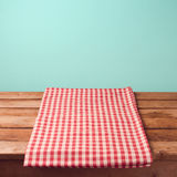 Empty wooden deck table and red checked tablecloth. Over mint wallpaper background royalty free stock photo