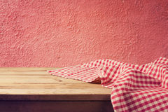 Empty wooden deck table with red checked tablecloth over red wall Stock Photos