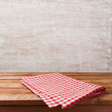 Empty wooden deck table with red checked tablecloth over rustic wall background for product montage display. Restaurant or kitchen interior stock images