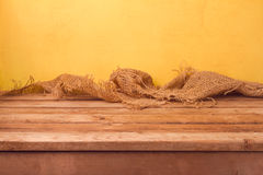 Empty wooden deck table and sackcloth over yellow wall background for product montage. Display royalty free stock photo