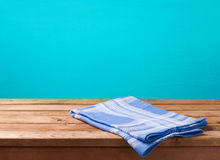 Empty wooden deck table with tablecloth over blue wall background for product montage Stock Image