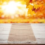 Empty wooden deck table with tablecloth over bokeh autumn leaves background stock photos