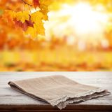 Empty wooden deck table with tablecloth over bokeh autumn leaves background royalty free stock photo