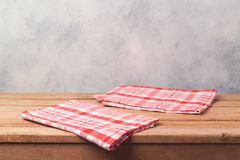 Empty wooden deck table with tablecloth over bright rustic background for product montage Stock Photos