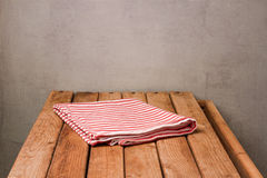 Empty wooden deck table with tablecloth over rustic background